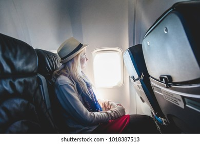 Young Caucasian Tourist Woman Alone Looking Outside and Sitting inside Airplane  While Going in Vacation