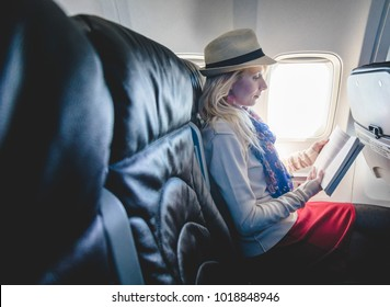 Young Caucasian Tourist Woman Alone inside Airplane and Reading a Book While Going in Vacation