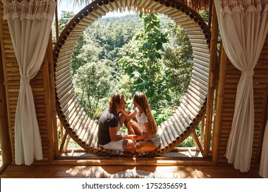 Young caucasian travel couple sitting in bamboo eco  house, nature and mountains on background. Man and woman sit on the window in bamboo bungalow and looking at mountains. Vaction on Bali island