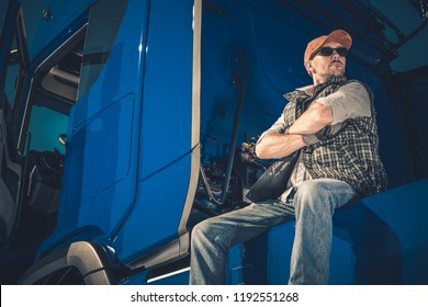 Young Caucasian Trucker Wearing Sunglasses Taking Break on the Truck Stop. Blue Modern Semi Truck.