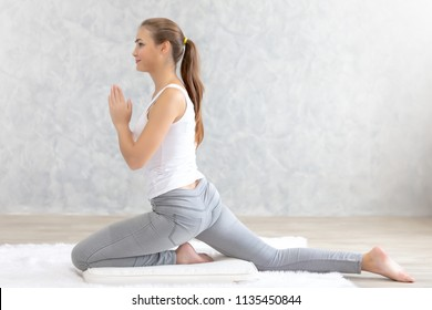 Young caucasian very attractive woman practicing yoga, sitting in Padmasana doing yoga exercise or Lotus pose or namaste pose. Working out on her bed.