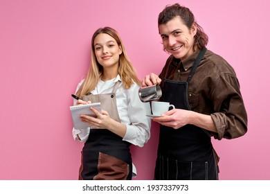 Jeunes serveurs caucasiens en tablier posant à la caméra isolés sur fond rose