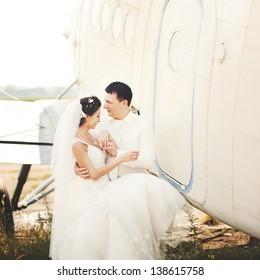 young caucasian wedding couple next to airplane