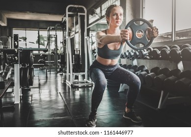 Young caucasian white woman doing workout with weight plate at the gym