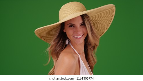 Young Caucasian woman in bikini and sunhat smiling on green screen