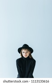 Young caucasian woman in black turtleneck and hat