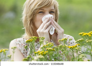 Young Caucasian woman blowing nose into tissue in front of flowers