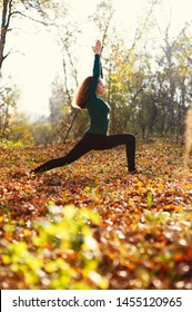 Young caucasian woman with brown hair practicing yoga in the autumn forest. View of a warrior pose.