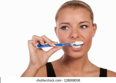 Young Caucasian woman brushing her teeth, portrait