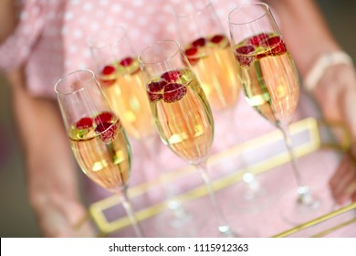 Young caucasian woman with champagne glasses on tray