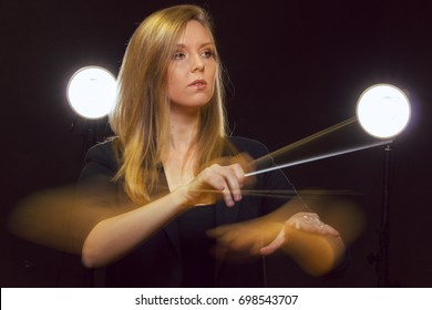 Young caucasian woman conductor gestures with baton and leaves light trails