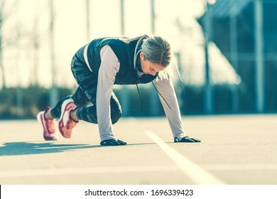 Young Caucasian woman doing stretching  exercises, preparing for run