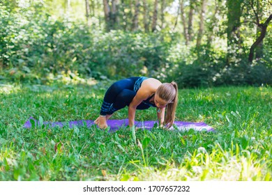 Young caucasian woman doing yoga exercises in summer city park.