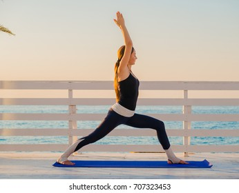 Young caucasian woman doing yoga asana in the nature on a wooden balcony or bridge overlooking sea. Woman doing practice on the ocean relaxing in nature. Girl in sports wear.