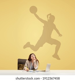 Young caucasian woman dreaming about future in big sport during her work in office. Shadow, silhouette of female basketball player on the wall. Becoming a legend. Inspiration, aspiration. Copyspace.
