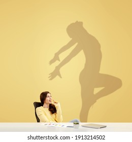 Young caucasian woman dreaming about future in big sport during her work in office. Shadow, silhouette of female dancer on the wall. Becoming a legend. Inspiration, aspiration. Copyspace.