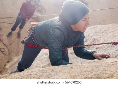 Young caucasian woman dressed for cold weather rock climbing in the desert climbs a cliff