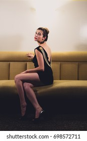 Young caucasian woman dressed like Audrey Hepburn poses in an empty bar