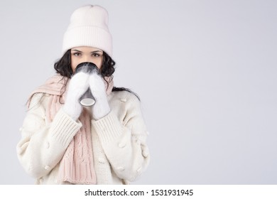 young caucasian woman drinking coffee trying to get warm. studio shot. Holding cup with hands in white mittens. with copy space