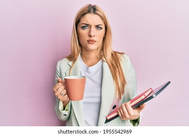 Young caucasian woman drinking a cup of coffee and holding laptop skeptic and nervous, frowning upset because of problem. negative person.