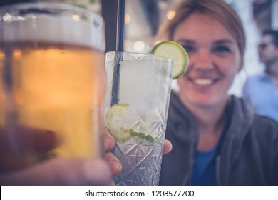 A young caucasian woman enjoying a glass of gin tonic with a lime and cheering with another person with a beer.POV view of a woman cheering with gintonic and beer