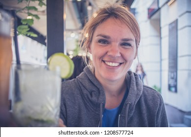 A young caucasian woman enjoying a glass of gin tonic with a lime and cheering with another person with a drink. POV view of a woman cheering with gintonic.