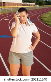 Young Caucasian woman exercising outside on a track at a high school sports complex late in the afternoon