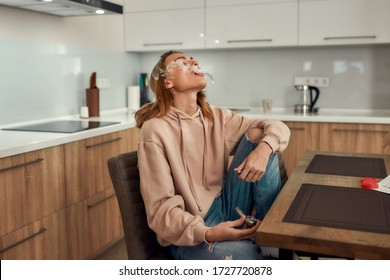 Young caucasian woman exhaling the smoke while smoking marijuana from a metal pipe, sitting in the kitchen. Red weed grinder on the table. Cannabis legalization concept