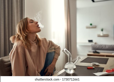 Young caucasian woman exhaling the smoke while smoking marijuana from a bong or glass water pipe, sitting in the kitchen. Red weed grinder and lighter on the table. Cannabis legalization concept