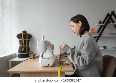 young caucasian woman fashion designer is sitting at home in her office at the table. Sewing machine. Measure the required piece of fabric with a flexible meter. Small business concept. 4k