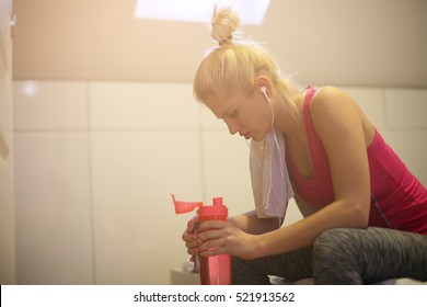 Young Caucasian woman filing tired, drinking water during workout at home.
