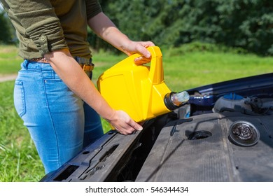 Young caucasian woman filling car motor with oil in yellow jerrycan