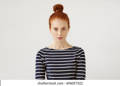 Young Caucasian woman with freckled skin, green eyes and ginger hair tied in bun, wearing sweater with stripes, looking confidently into camera, isolated over white background. People and lifestyle