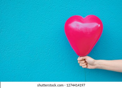 Young caucasian woman girl holds in stretched hand bright pink heart shape air balloon on turquoise painted wall background. Valentine love charity donation concept. Vivid Colors. Urban Atmosphere