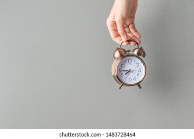 Young caucasian woman girl holds in hand alarm clock on gray wall background. Waking up energy new day self-organization time management change concept. Poster template