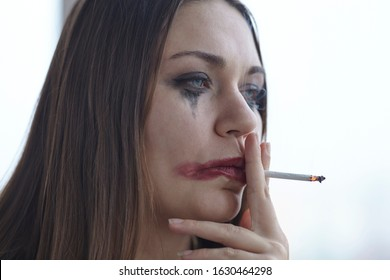 Young caucasian woman with greased sleazy make up smoking in stress or melancholy mood. Domestic violence concept, boozing, hangover. Сlose up portrait with all imperfections of real skin.