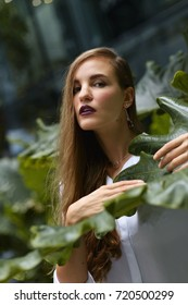 Young caucasian woman in a green forest environment with large exotic leafs