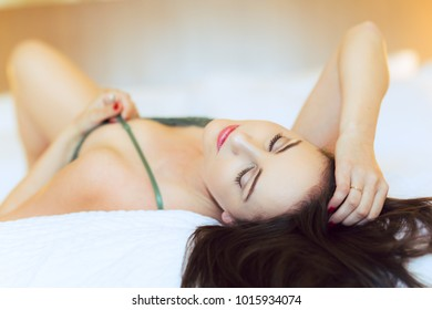 Young caucasian woman in green lingerie poses on bed