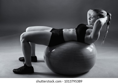 Young caucasian woman with a gym ball doing abs crunches