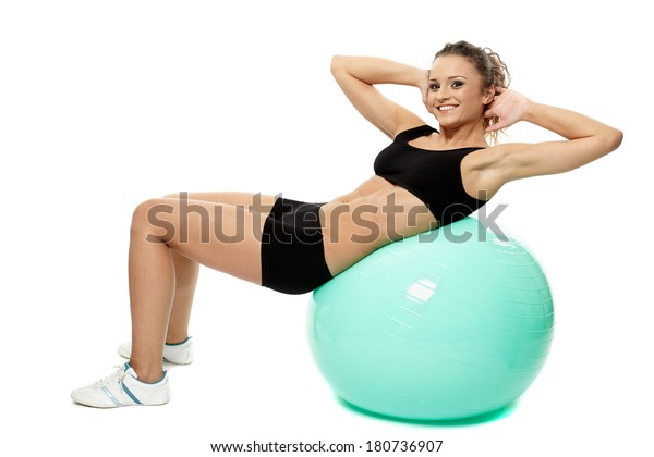 Young caucasian woman with a gym ball doing abs crunches, isolated on white