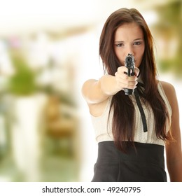 Young caucasian woman with hand gun