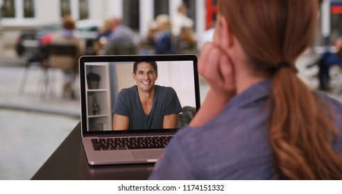Young Caucasian woman having video conversation with white man outside on laptop
