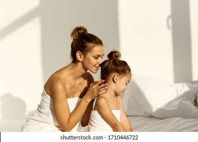 A young caucasian woman with his daughter on a bed at home in the morning, wearing in towel