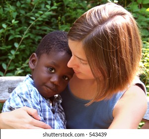 Young caucasian woman holding a beautiful African American child.