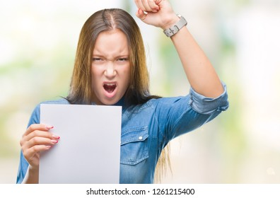 Young caucasian woman holding blank paper sheet over isolated background annoyed and frustrated shouting with anger, crazy and yelling with raised hand, anger concept