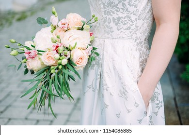Young caucasian woman holding bouquet of fresh flowers made of roses, eustoma flowers and green leaves. Summer family event.