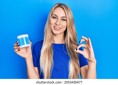Young caucasian woman holding earwax cotton removers doing ok sign with fingers, smiling friendly gesturing excellent symbol