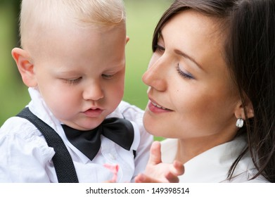 young Caucasian woman holds her baby son, closeup
