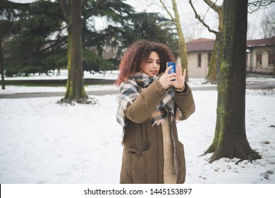 young caucasian woman interacting with her smartphone in park – new generation, technology, free time