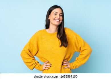 Young caucasian woman isolated on blue background posing with arms at hip and smiling